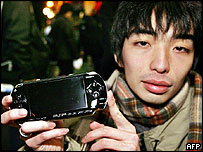 The first customer to buy a PSP leaves a Tokyo electronics shop