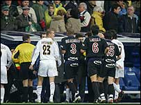 The referee leads the players off the pitch following the bomb alert