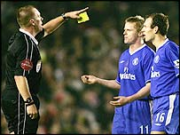 Referee Graham Poll waves away angry Chelsea players after Thierry Henry's goal