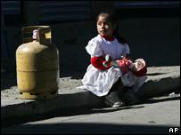 Una ni�a boliviana sentada al lado de una bombona de gas