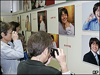 Japanese fans, mostly over 40, take pictures of their Korean idol Bae Yong-joon at a photography exhibition in Tokyo, 21 Oct 2004