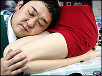 "A sales clerk introduces 'Hizamakura"", or lap pillow, at Hakuhinkan toy shop in Tokyo, 13 December 2004"