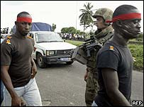 Anit-French prtoestors pass by a French soldier in Abidjan