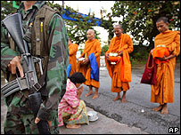 A Thai soldier guards a group of Buddhist monks during their early morning rounds in Bacho, Thailand (June 2005)
