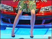 Model sitting on the bonnet of a Fiat Idea