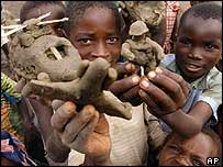 Children show their models of a helicopter and a solider in eastern DR Congo
