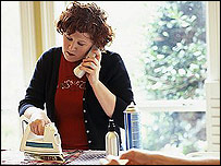 Woman on phone while ironing