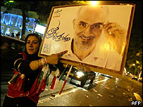 Woman points to poster of reform candidate Moin in Tehran as cars drive past