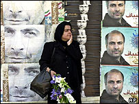 Iranian woman holding flowers stands between posters of candidate Mohammad Baqer Qalibaf