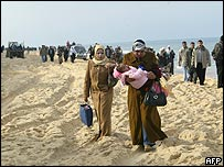 Palestinians walk along the beach after Israeli troops blocked the road between Gaza and Khan Younis