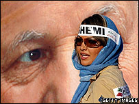 Woman wearing stickers in support of Rafsanjani walks past poster of him