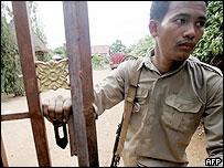 An armed Cambodian policeman guards the gate of Siem Reap International School in Siem Reap, 16 June 2005