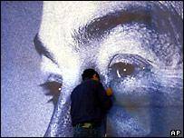 A man puts up a poster of Iyad Allawi