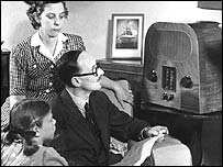 A family grouped round a wireless set listening to BBC radio in 1947