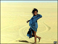 A girl walks in the midday heat in the Sahara Desert