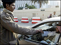 Saudi policeman checks driver's papers at security checkpoint in Riyadh