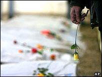 Man holds a flower near remains of 44 bodies