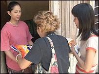 Zainun Jainul, receiving bags of rice from local volunteers