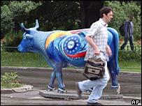 Romanian man runs past fake cow painted with EU symbol