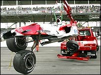 Ralf Schumacher's Toyota is lifted off the track after crashing in Indianapolis
