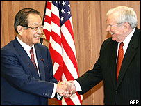 Japan's Defence Agent Director General Yoshinori Ono (L) shakes hands with US Ambassador to Japan Howard Baker 17/12/2004
