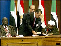 Mohammed Osman al-Mirghani (R), head of the opposition National Democratic Alliance,  signs the agreement.