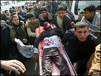 The body of a Palestinian is carried into a hospital in the southern Gaza Strip refugee camp of Khan Yunis