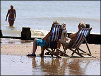 Sunbathers in deckchairs on the beach in Eastbourne, East Sussex