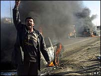 A man cheers next to a burning truck after an attack by insurgents on 9 December