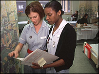 Two nurses examine a patient's case notes