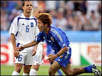 Masashi Oguro celebrates as he runs past Angelo Basinas of Greece after scoring