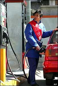 An attendant fills a car at a Beijing petrol station