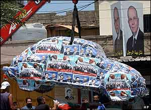 A car covered in Hariri posters is removed by traffic police in Tripoli, Lebanon