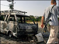 Israeli security man inspects a burned Israeli van after it was attacked by Palestinian militants outside the northern West Bank town of Baqa al-Sharqiya