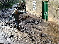 A resident negotiates a sea of mud at Hawnby, North Yorkshire