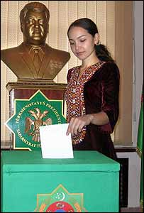 A woman votes in Ashgabat - Mr Niyazov's statue is seen in the background