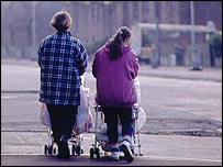 Two mothers pushing wheelchairs
