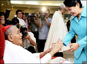 Philippine President Gloria Arroyo (R) congratulates Jaime Cardinal Sin (L) for the special Papal award after a mass at the cardinal's residence in Mandaluyong city suburban Manila, 28 April 2005.