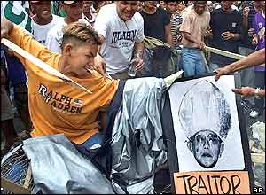 A supporter of Philippine President Joseph Estrada thrusts a poster of Cardinal Jaime Sin before setting a fire in Manila's Makati business district Friday, Jan. 19, 2001.