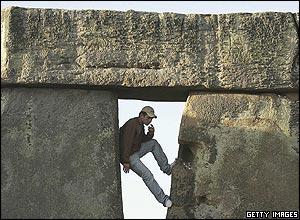 Man climbs the stones at Stonehenge