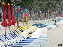 Thai woman waits for customers in a line of chairs at Patong beach in Phuket, 16/6/05