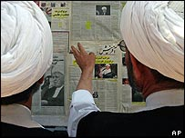 Two clergymen read newspaper articles about the election in the city of Qom