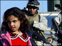 An Iraqi girl stands in front of US marines who arrived to visit civilians living at a cement factory at the edge of the city of Falluja, Iraq