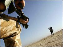 A British soldier stops a civilian near Baghdad