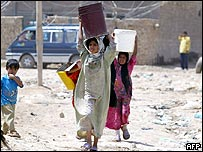 Iraqi girls carry home water in cans