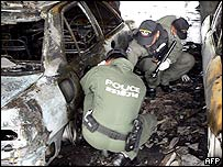 Thai paramilitary officers inspect charred cars following a bomb blast in the parking area of a bank in Rangae district of Thailand's disturbed southern Narathiwat province, 21 June 2005