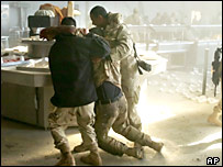 US soldiers help a wounded colleague after an attack on a mess tent in Mosul