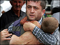 A Beslan resident carries an injured child