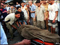 Iraqis take away the body of a dead man on a stretcher in Baghdad
