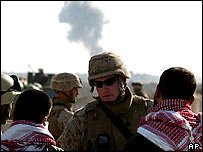 US soldier speaks to residents of Falluja with smoke in the background